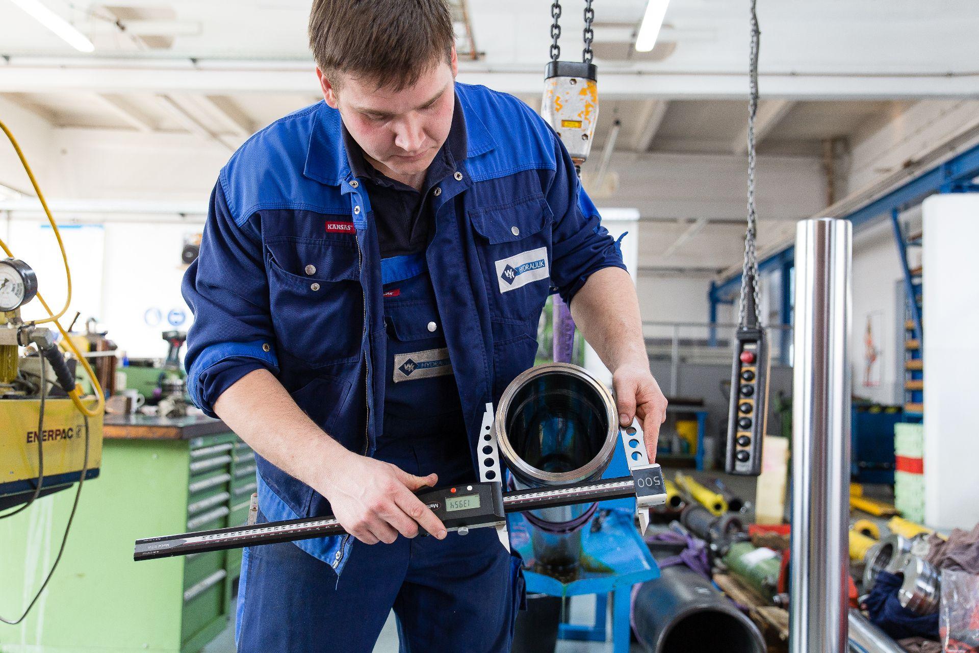 ein Mitarbeiter beim Messen des Außendurchmessers eines Hydraulikzylinders
