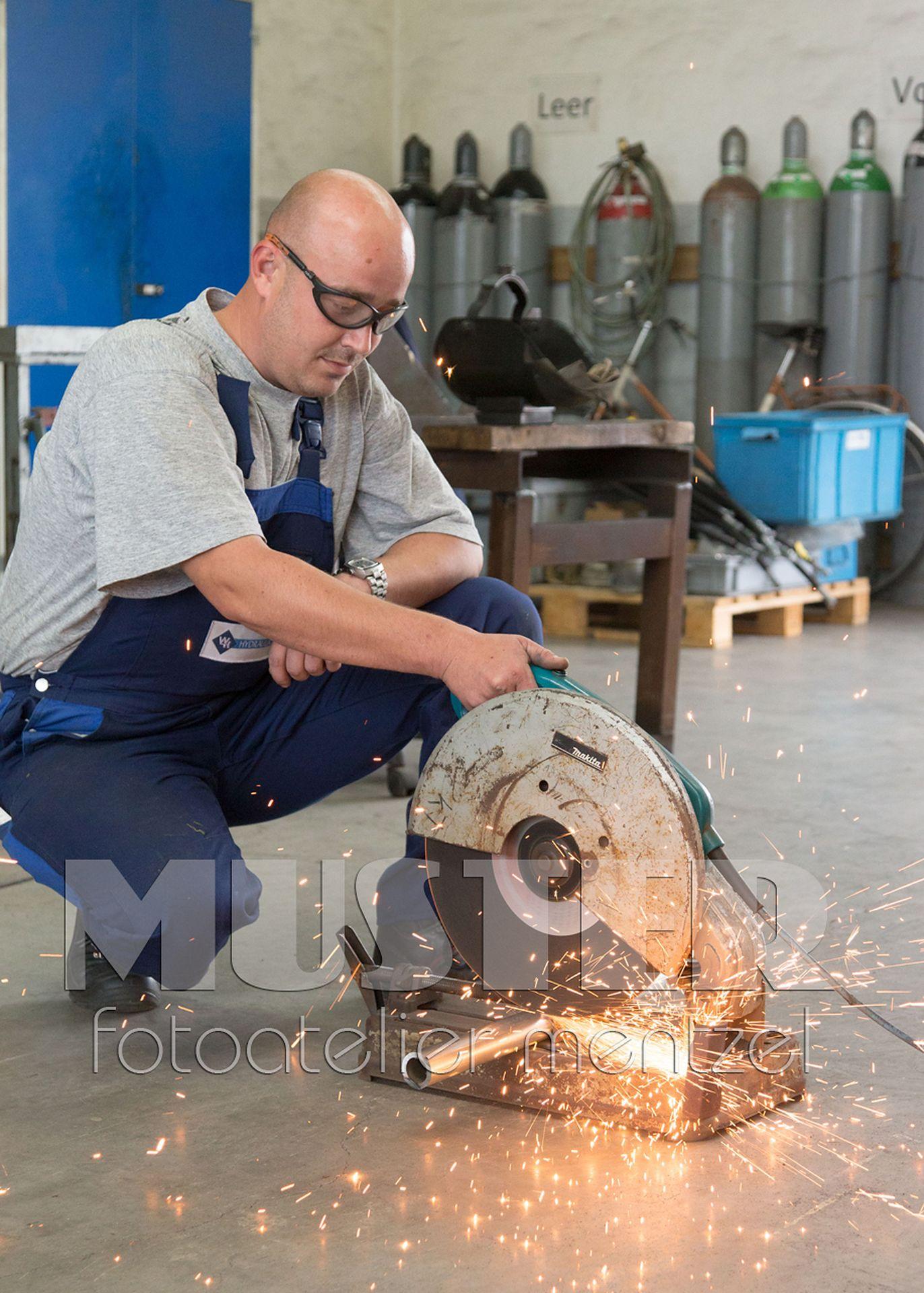 Ein Mitarbeiter trennt ein Stück von einem Rohr