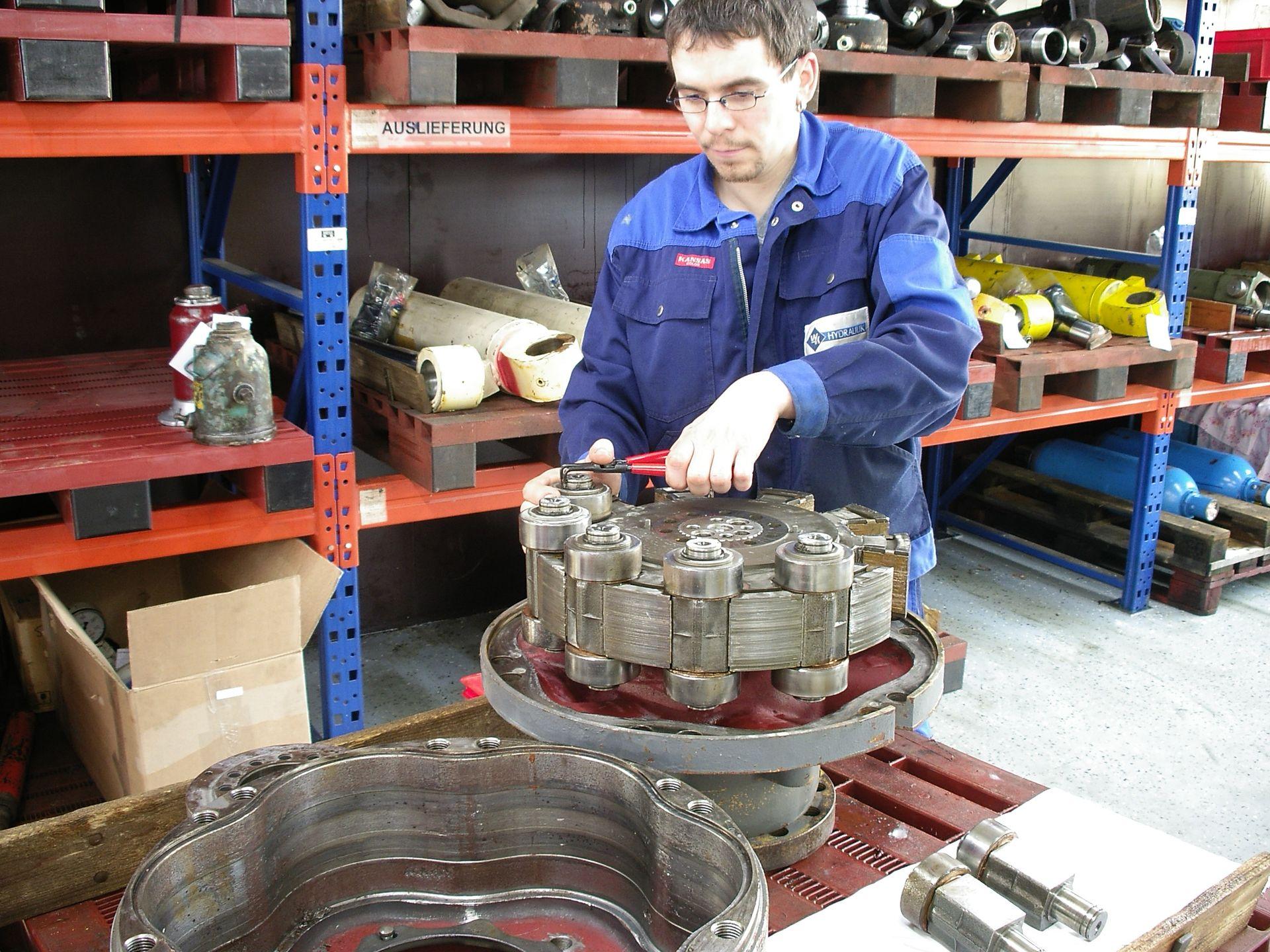 Eine WK HYDRAULIK-Mitarbeiter demontiert eine Hydraulikpumpe